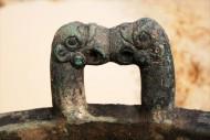 массивный литой бронзовый котел с ручками в виде геральдического изображения голов двух грифонов, смотрящих друг на друга. Изображения грифонов выполнены в традициях скифо-сибирского звериного стиля